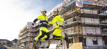To menn i arbeidsklær hopper foran bygg under oppføring.