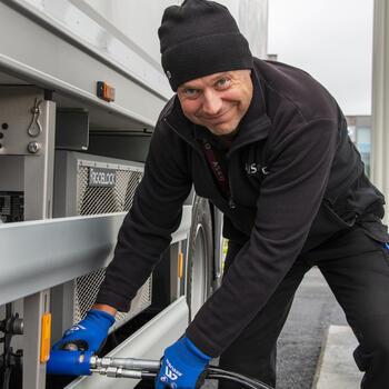 Mann som fyller gass på lastebil.